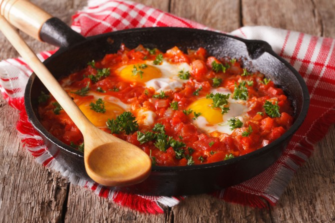 Homemade breakfast shakshuka of fried eggs with tomato close-up.